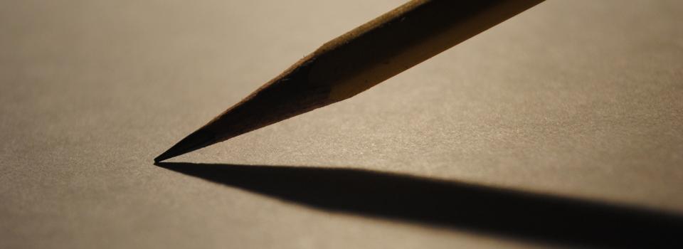 Potlood voorzichtig rustend op een leeg vel papier